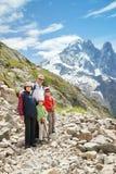 La famille de quatre personnes restant sur la traînée en montagnes Image libre de droits
