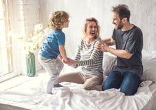 La famille de sourire partage le moment joyeux ensemble dans la chambre à coucher Photographie stock libre de droits