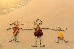 La famille de trois personnes dessinées sur le sable échouent avec la vague molle Voyage Images libres de droits