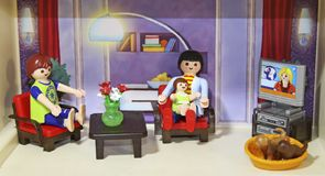 La famille des poupées se reposent le soir devant la TV Photo libre de droits