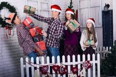 La famille drôle avec des cadeaux dans leurs mains s'attaque à Noël Photographie stock
