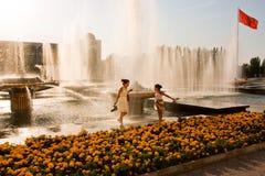 La famille drôle sautent près des fontaines un jour chaud Image stock
