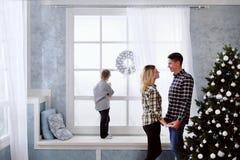 La famille du père et de la mère rencontrent la nouvelle année à la maison photographie stock libre de droits