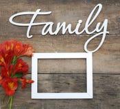 La FAMILLE en bois blanche d'inscription marque avec des lettres le fond en bois rustique de fleurs d'Alstromeria de rouge orange Photos libres de droits