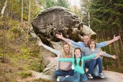 La famille est heureuse de poser pour la photo de souvenir devant la roche sur le fond de forêt Photographie stock