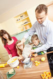 La famille fait des biscuits cuire au four Photographie stock