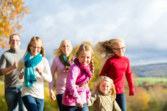 La famille font un tour dans la forêt d'automne Images stock