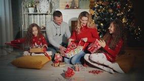 La famille gaie de quatre personnes ouvrent des cadeaux de Noël Nuit de nouvelle année au pied de l'arbre de Noël banque de vidéos