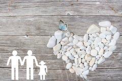 La famille gaie sur le fond en bois avec le blanc lapide le coeur et le papillon bleu Photos stock