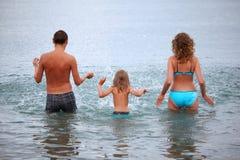 La famille heureuse éclabousse l'eau restant en mer photographie stock