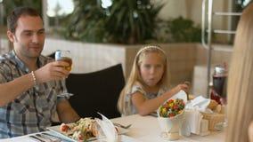 La famille heureuse avec des enfants font tinter des verres avec du jus pour le dîner clips vidéos