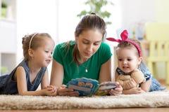 La famille heureuse avec des enfants a lu une histoire s'étendant sur le plancher dans la salle d'enfants photo stock