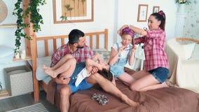La famille heureuse avec deux filles se reposent dans la chambre à coucher, le jeu et le rire, mouvement lent banque de vidéos