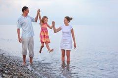 La famille heureuse avec la fille sur la plage, parents soulèvent la fille Photo libre de droits