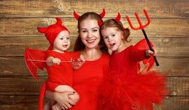 La famille heureuse avec le diable de costumes se prépare à Halloween Image libre de droits