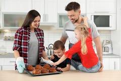 La famille heureuse avec le plateau du four a fait des petits pains cuire au four photo libre de droits