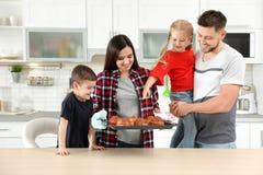 La famille heureuse avec le plateau du four a fait des petits pains cuire au four photographie stock