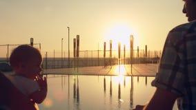 La famille heureuse avec trois enfants admirant le coucher du soleil s'est reflétée dans la surface de la piscine banque de vidéos