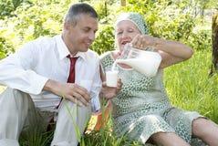 La famille heureuse boit du lait de vache frais Image stock