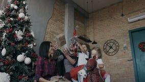 La famille heureuse célèbre Noël à la maison La jeune famille s'asseyant à côté de l'arbre de Noël et jette joyeux  banque de vidéos