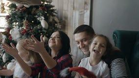 La famille heureuse célèbre Noël à la maison La jeune famille s'assied sur le plancher à côté de l'arbre de Noël et joyeux banque de vidéos