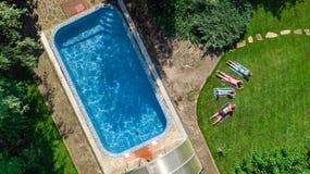 La famille heureuse détendant par la piscine, la vue aérienne de bourdon d'en haut des parents et les enfants ont l'amusement des images libres de droits