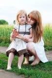 La famille heureuse dans l'herbe verte prennent un Teaparty Photographie stock