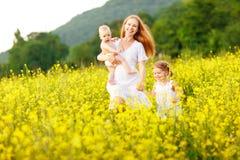 La famille heureuse de la mère et les enfants courent dans le pré du jaune Photographie stock