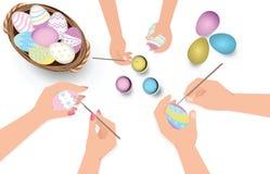 La famille heureuse de Pâques ayant la peinture d'amusement et décorent des oeufs pour le holid Photos libres de droits