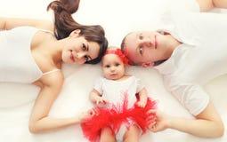 La famille heureuse de portrait enfantent ensemble, père et bébé se trouvant sur le lit à la maison Photo stock