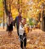 La famille heureuse est en parc de ville d'automne Enfants et parents courant avec des feuilles Ils posant, souriant, jouant et a photo libre de droits
