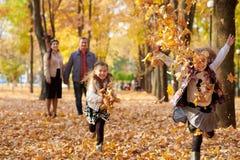 La famille heureuse est en parc de ville d'automne Enfants et parents courant avec des feuilles Ils posant, souriant, jouant et a images libres de droits