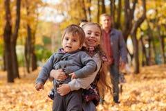 La famille heureuse est en parc de ville d'automne Enfants et parents Ils posant, souriant, jouant et ayant l'amusement Arbres ja photo libre de droits