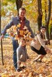 La famille heureuse est en parc de ville d'automne Enfants et parents Ils posant, souriant, jouant et ayant l'amusement Arbres ja photographie stock
