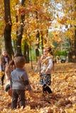 La famille heureuse est en parc de ville d'automne Enfants et parents Ils posant, souriant, jouant et ayant l'amusement Arbres ja photos libres de droits