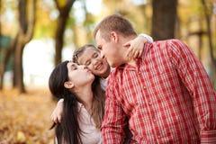 La famille heureuse est en parc de ville d'automne Enfants et parents Ils posant, souriant, jouant et ayant l'amusement Arbres ja photographie stock libre de droits