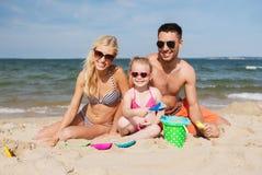 La famille heureuse jouant avec le sable joue sur la plage Images stock