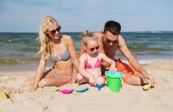 La famille heureuse jouant avec le sable joue sur la plage Photographie stock