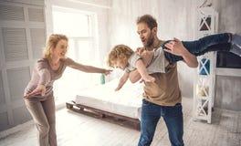 La famille heureuse joue ensemble dans le jeu d'avion dans le dortoir Images libres de droits