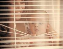 La famille heureuse, l'amour, femme de confiance avec le sourire d'enfant à la fenêtre shutters Image stock