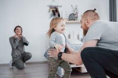 La famille heureuse a l'amusement à la maison La mère, le père et la petite fille avec le jouet de peluche apprécient étant ensem Photos libres de droits