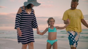 La famille heureuse marchant sur la côte d'océan silhouette le coucher du soleil banque de vidéos