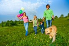 La famille heureuse marche avec les ballons et le chien en parc photographie stock libre de droits