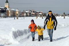 La famille heureuse marche en hiver Photo stock