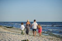 La famille heureuse marche le long du bord de la mer tenant des mains photos libres de droits