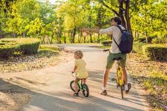 La famille heureuse monte des vélos dehors et le sourire Engendrez sur un vélo et un fils sur un balancebike Image libre de droits
