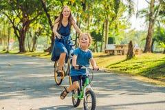 La famille heureuse monte des vélos dehors et le sourire Maman sur un vélo et un fils sur un balancebike Photo stock