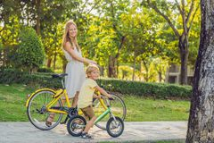 La famille heureuse monte des vélos dehors et le sourire Maman sur un vélo et un fils sur un balancebike Photos libres de droits