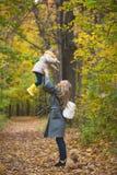 La famille heureuse ont l'amusement marchant dans le parc d'automne - les mains de mère les jets blonds de fille photos libres de droits