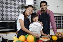 La famille heureuse ont le papa, la maman et leur petite fille faisant cuire le pouvoir adiathermique images libres de droits